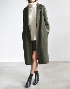white knit turtleneck sweater with skirt and long green coat. Pointed toe boots.