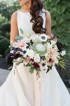 Wedding at Tranquility Farm, Purcellville, VA. Stunning bridal bouquet with pops of burgundy and black, with king protea, dahlia, and anemone by Lark Floral