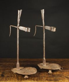 A Pair of Wrought Iron Candle / Rush Holders on tray bases with voluted strap feet, 22 ins (56 cms) in height.
