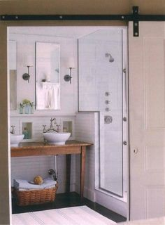 Love the uniqueness of this vanity (old pine table), two vessel sinks, unadorned mirrors, split faucets mixed with white subway tile and clean lines of glass shower; iron sconces; cubbies for beautiful bottles; dark floors -- sliding barn doors -- really really lovely and different (Molly Frey Design)