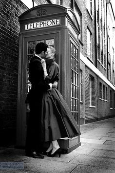 Romantic London. Vintage kissing in front of a telephone box.
