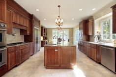Long rectangular kitchen with rich wood cabinetry, stainless steel appliances and matching island.