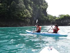 Carolina and Arellys paddling on the Pacific Ocean near Manuel Antonio's coast.