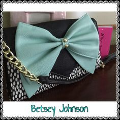 """Betsey Johnson Crossbody/Shoulder Bag/Wallet Black and white dot exterior with a sold black flap over snap closure with an exquisite mint bow with two gold tone semicircles attached. Interior zipper pocket in middle with two openings on each side w/ 1 side having 8 creditcard slots & the other side 4 having creditcard slots with an additional long slit opening. 8""""L x 5""""H x 1""""D. Detachable straps. Total strap drop is 23"""" with the first 4"""" on each side being gold tone. Brand new, with tags…"""