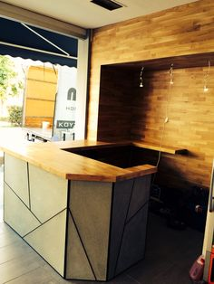 This is an espresso bar I made In Athens.infont there is a geometric  reinforced concrete panel with black aluminum geometric shapes.on the wall I put oak wood.
