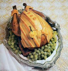 One image features a chicken on a bed of grapes, topped with pastry designed to look like a dinner jacket