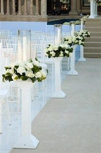 The ceremony aisle is lined with covered white chairs and candles in hurricanes, surrounded by white roses.