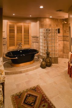 Luxury bathroom design with mood lighting, black free-standing tub in wood base, separate walk-in shower and extensive wall tiles