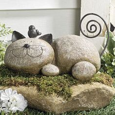 "Cat Statue - This happy kitty doesn't mind having a little bird resting on its head. Made of lightweight resin, this feline has wire whiskers and a coiled tail, too. Measures 9"" wide."