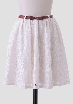 A Ruchette must-have, this ivory skirt is adorned with a sheer lace overlay and an elastic waistband for the perfect fit. Accented with an optional cognac-hued faux leather belt with a bow and go...