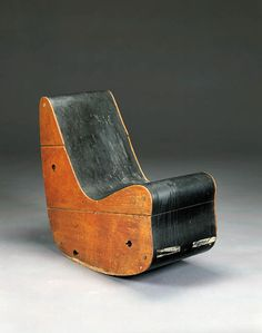 AN ASH AND LINOLEUM ROCKING CHAIR -   Frederick Kiesler, Circa 1942 -  Of organic form with ash-paneled sides enclosing a black linoleum continuous seat  approximately 34in. (86.3cm.) high, 15in. (39.4cm.) wide, 34in. (86.3cm.) deep