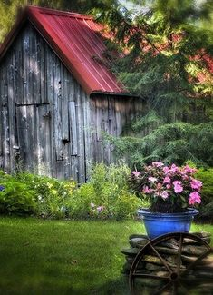 Red roof barn, blue flower pot on stones, wheel