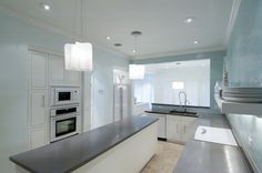 Designed by Terri Pakravan   White cabinet kitchen, concrete countertop, tuquoise glass tile