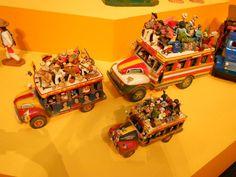 """Tres """"chivas"""" o camioncitos polleros de Colombia representados en barro, por la artesana Cecilia Vargas."""