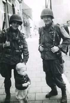 "Caption: ""US soldiers stand with a little boy in Eindhoven, Netherlands - September 1944. The man on the right was later identified, 62 years after the photo was taken by veterans visiting Eindhoven, as 1LT Herbert Viertel, B Company, 1st BN, 506 PIR, 101st Airborne Division."""