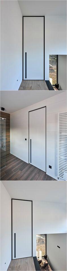 "White interior door from floor to ceiling with a black anodized ""BKO"" door frame and a built-in door handle."