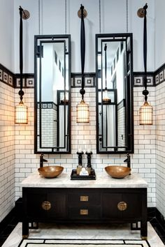 Black and cream dramatic bathroom, tall mirrors, hanging pendants from tall ceilings, black and cream, furniture as vanity, gold, mosaic tile detail with subway tile.