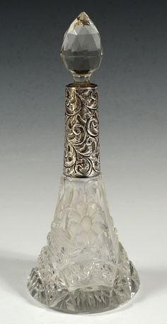 CUT GLASS PERFUME BOTTLE W/ STERLING SILVER COLLAR. Circa 1910 cut glass bottle with faceted stopper and a long, hand chased sterling silver collar stamped with Birmingham hallmarks.