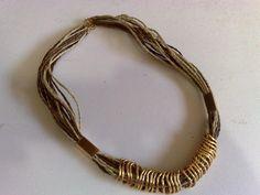 Colar curto feito com fios de sisal marrom e bege com elos e detalhes dourados