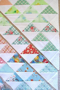 Simple quilt assembly: sew strips of colour to white - both edges, cut triangles through both layers - zig zag from seam to seam, press open, turn and arrange layout, sew blocks into strips, then sew strips together.