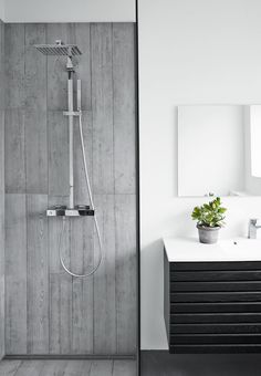 Nordic and stylish bathroom without flaws - clear lines, transparent glass wall and a green plant to finish the look. Simplicity at its best!
