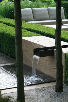 Minimalist Travertine and Steel Water Feature Surrounded by Simple Boxwoods and Modern Landscaping · ApePlus.com