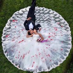 Wedding dress spread out in a circle with bride and groom on the ground. Beautiful!