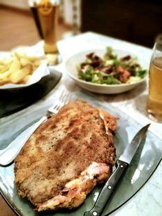 Cachopo Asturiano. Ingredientes: Dos filetes de buey irlandes, rellenos de jamón ibérico de bellota, jamón york, queso havarti, y doble empanado, frito en aceite de oliva virgen extra. Ensalada y patata frita con corte artesano.