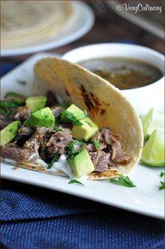 Meat cooks all day in an awesome tomatillo salsa, then shredded, and topped with ripe avocado and tangy lime juice. So good! #slowcooker #crockpot