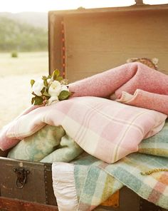 Old fashioned plaid blankets in a vintage trunk.