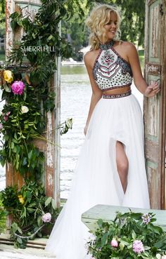 The Sherri Hill 50075 is a delightful two-piece prom dress that catches attention with its colorful floral beadwork. Multi-toned beading adorns the crop top, also featured with a high halter neckline that leaves a semi-open back. A beaded band tops the layered high slit skirt, which plunges sumptuously into the floor.