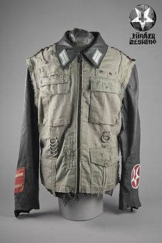 """This up-cycled Military Jacket is made from German army vintage supplies and deer skin. It features the Junker trademarked patched body and has a unfinished hem and wrist. Also featured are vintage army patches and spray painted squad number. This is a Junker coat that will last a lifetime. This is not a thin """"fashion"""" leather made overseas in mass.Each piece is unique. No two will be exactly the same.Often imitated never duplicated. Art for Life★ WEAR IT L..."""