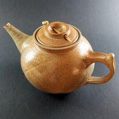 This beautiful orange teapot is wheel thrown and finished by hand. It is made from stoneware clay, shino glazed gas fired in reduction.  The