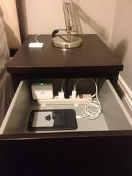 Put a power strip in the top drawer of your nightstand to charge & organize