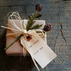 Natural Holiday Gift Wrap with sprig of greens, brown kraft paper, raffia and tag