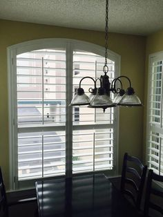 "Plantation shutters arched top window with traditional tilt bar, 4½"" louvers, and divider rails. Designed and installed by Blinds, Shutters and More LLC of Niceville, FL"