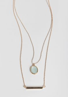 This lovely layered necklace features a gold-toned bar pendant and a light mint-hued gem pendant.