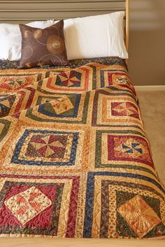 PINWHEEL SONG by Christina McCourt: 'Tis the season for autumn bed-size quilt patterns! Bring on the pumpkins, apple cider, and beautiful fall prints. Rich fabrics were fashioned into two favorite Pinwheel blocks for this traditional autumn quilt. The warm hued prints that are used in these quilt blocks make for a cheerful and lively quilt. Frame it with a rich dark green border to bring it all together. Perfect for your seasonal décor or year-round, if you please!