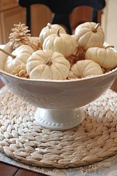 Simple white pumpkins and bleached pinecones in a footed bowl.