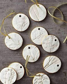 Gorgeous pressed herb polymer clay ornaments or gift tags! Working atop parchment paper roll out polymer clay until its about 1/4-inch thick. Position herb sprigs on top of the clay. Gently roll over the herbs with a rolling pin then peel greenery out of the clay. Cut out ornaments and carefully place them on a cookie sheet. Use a drinking straw to cut holes for ribbon hangers. Bake following manufacturers directions; let cool. Squeeze a thin line of paint onto a waxed paper plate. Roll orna…