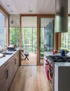 """In the kitchen, the cabinetry is walnut veneer with a weathered finish applied by cabinetmaker David Rogers. """"The process involved sanding and rubbing in stain as well as adding a clear finish,"""" project architect Eero Puurunen says."""