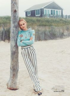 Leaning on a tree, the model wears embellished sweater and striped pants from Tommy Hilfiger
