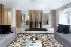 Projeto de hall de entrada de condomínio residencial com piso porcelanato, paredes com painéis de mdf e espelhos, tapete de couro natural, vasos com plantas naturais. Projeto de Rosa Pinheiro.