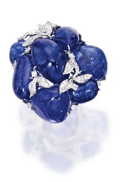 18 KARAT WHITE GOLD, TANZANITE AND DIAMOND RING, SIFEN CHANG Designed as a cluster of seven tumbled tanzanite beads weighing 80.50 carats, accented by vines set with round diamonds weighing .68 carat, size 6¼, with Chinese characters for Sifen Chang. With signed box.