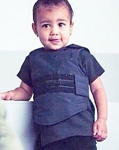 New fashion statement? As she was sitting front row at her father Kanye West's Adidas New York Fashion Week collection on Thursday, Feb. 12, 20-month-old North West was wearing a bulletproof vest from her dad's line.