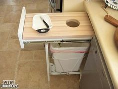Take out a drawer and add a trash can pullout to the below cabinet. Awesome!