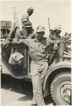 A soldier with the Afrika Korps poses next to a Fiat SPA Camionetta AS42 Sahariana long range reconnaissance vehicle