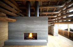 """Rough hewn logs and concrete fireplace in loggia of  Armando Ruinelli's """"Redevelopment of a Barn"""""""