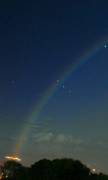 Moonbow and Venus imaged by Rob Ratkowski (photography) in May 2004.    Moonbows are very rare. The moon must be bright and not too high, the sky must be dark else the faint bow will not be visible and there must be rain in the direction opposite the moon.   Orion was setting when Rob took this spectacular image, Venus is the bright object inside the bow. Mars is above it to the left and Saturn is above Mars and outside the primary. Capella is the bright star to the right (north) of Venus.