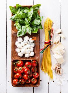 Italian flag colors with green basil, white mozzarella, red tomatoes, parmesan and spaghetti